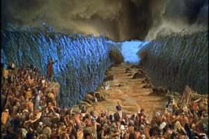 """El pueblo quiteño atravesando el bulevar en época lluviosa. Sobre una piedra se puede ver al burgomaestre hablando de la """"sociabilización de espacios""""."""